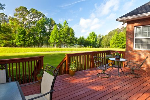 red outdoor timber deck with luscious garden at carpenters wollogong